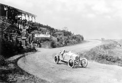 "French Grand Prix near Lyon on 4 July 1914. The Mercedes Grand Prix racing car of the eventual winner, Christian Lautenschlager (start number 28), entering the Piège de la Mort (""Death Trap""), around three kilometres from the starting/finishing line. Daimler-Motoren-Gesellschaft achieved a triple victory with its Mercedes Grand Prix racing cars, in the sequence Christian Lautenschlager, Louis Wagner and Otto Salzer."